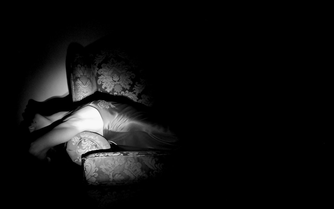 woman lying across a chairin the dark, lighted with a flashlight